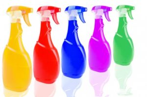 a row of multi colored spray bottles of cleaners